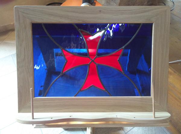 vitrail inséré dans un lutrin en bois avec la croix des templiers