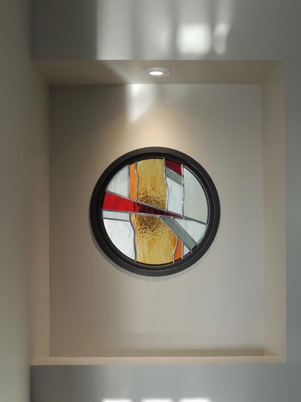 vitrail moderne posé dans un œil de bœuf métallique avec pare closes