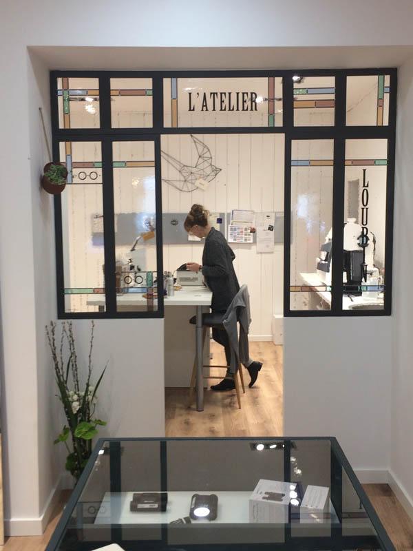 verrière en vitrail séparant une pièce d'atelier d'une boutique